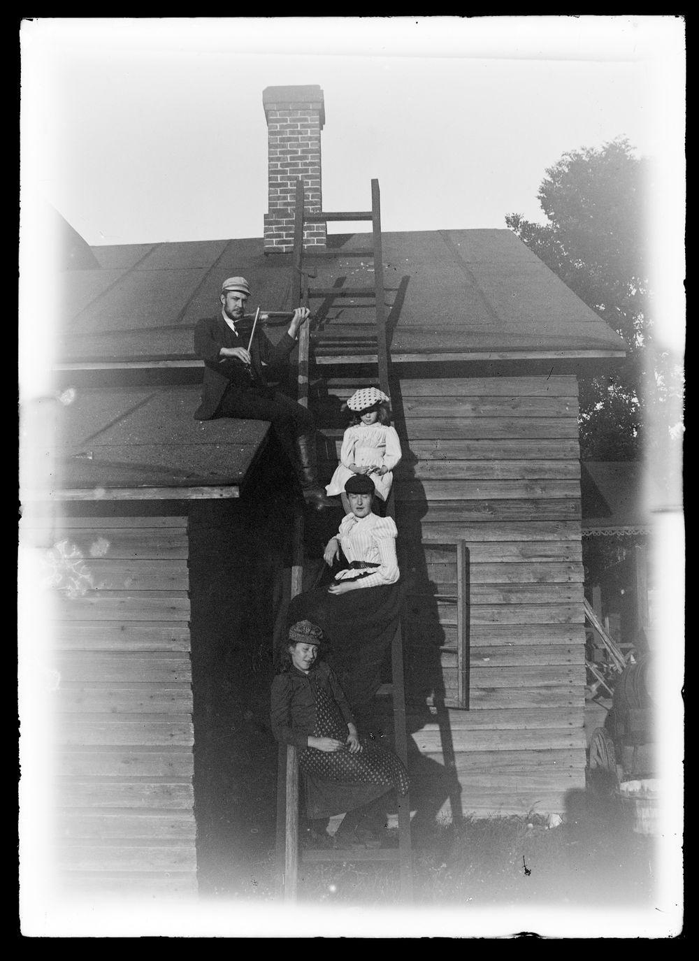 Paul Simberg soittaa viulua Keltaisen huvilan katolla, Blenda Simberg ja todennäköisesti Elma ja Elsa Simberg tikapuilla