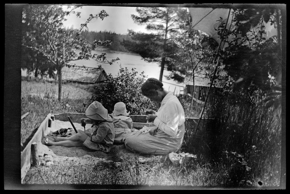 Tom ja Uhra Simberg leikkivät hiekkalaatikolla Pellingissä, tuntematon naishenkilö ompelutöiden äärellä