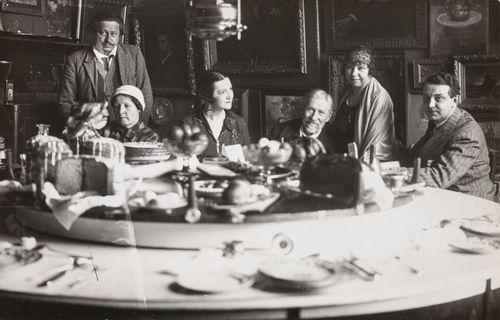 Penaty-huvilan ruokasalissa. Taustalla seisoo Juri Repin, pöydän ääressä Juri Repinin vaimo Praskovja, tuntematon naishenkilö, Ilja Repin, tytär Vera Repina ja tuntematon mieshenkilö