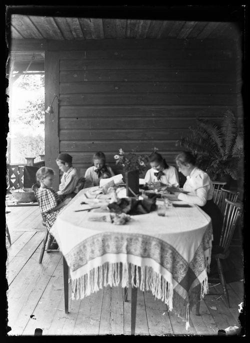 Guido, Elsa ja Elma Simberg lukemassa Keltaisen huvilan kuistilla, seurueessa myös kaksi tuntematonta henkilöä