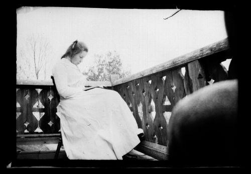 Elsa Simberg lukemassa Keltaisen huvilan parvekkeella