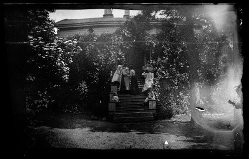 Naisia ja lapsia puutarhan portailla