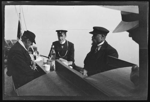 Matkalla Viroon Osmussaarelle, Hugo Simberg valokuvaa, keskellä univormussaan kapteeni Carl Alfthan ja hänen vieressään herrat Holman ja Vånnback, oikeassa kulmassa näkyy Werner Åströmin olkihatun reunaa