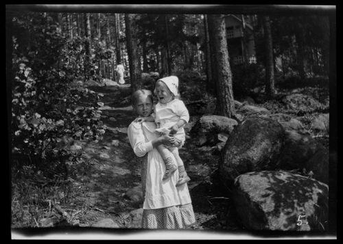 Lastenhoitaja ja Tom Simberg Selkärannan ateljeen laiturille johtavalla polulla, taustalla todennäköisesti Anni Simberg