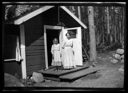 Lastenhoitaja ja tuntematon nainen Selkärannan ateljeen keittiömökin portailla