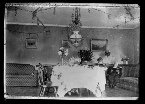"""Juhlakoristelu Keltaisen huvilan """"Biljardihuoneessa"""", Niclas Simberg lukemassa sohvalla."""
