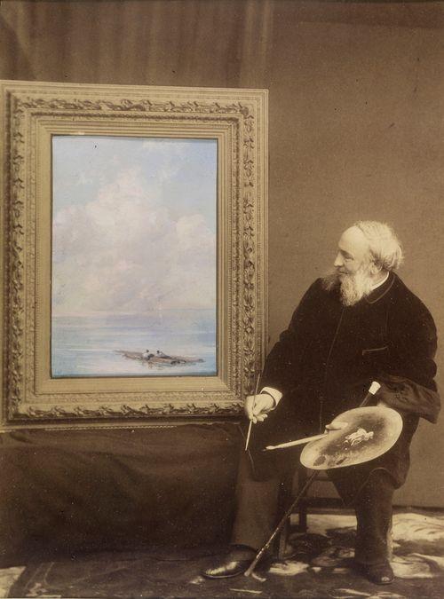 Omakuva, valokuva taiteilijasta ja kehyksestä, jonka aukossa jokimaisemaa esittävä öljymaalaus